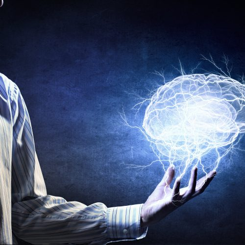 A man holding a brain that is made out of light and electricity.