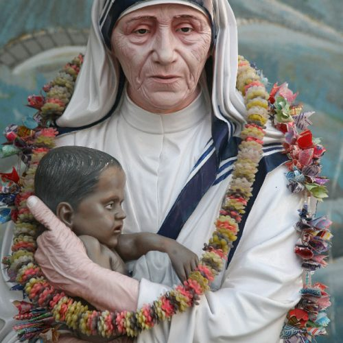 A statue of mother Teresa holding a baby in her hands.