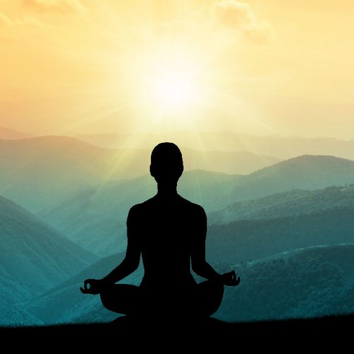a silhouette of a woman who is meditating on top of a hill.