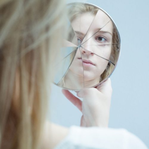 a woman is holding a shattered mirror, looking at her reflection in it.